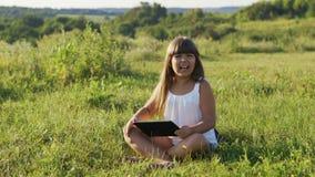Los mosquitos tienen interferir una niña que juega en una tableta digital en naturaleza almacen de metraje de vídeo