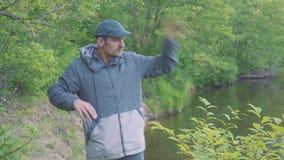 Los mosquitos y los escarabajos atacan a un hombre joven cerca del río Un hombre está agitando sus manos desesperadamente almacen de video