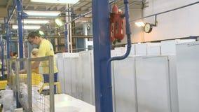 Los movimientos de la cámara a lo largo de la planta de fabricación con el refrigerador y la gente trabajan almacen de metraje de vídeo
