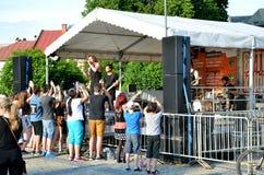 Los músicos juegan en la pequeña etapa, grupo de palmada de los fans sus manos, él son tiempo soleado Imágenes de archivo libres de regalías