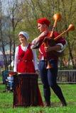 Los músicos - mujer y hombre - en trajes históricos se realizan en un parque Imágenes de archivo libres de regalías