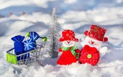 Los muñecos de nieve alegres en un fondo plateado del árbol del Año Nuevo con una carretilla llena de la Navidad juegan en la nie Fotografía de archivo libre de regalías