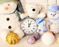 Los muñecos de nieve, los osos de peluche y las bolas del árbol de navidad acercan al despertador foto de archivo libre de regalías