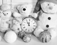 Los muñecos de nieve, los osos de peluche y las bolas del árbol de navidad acercan al despertador imagen de archivo