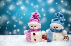 Los muñecos de nieve se juntan con el fondo azul del invierno Fotografía de archivo libre de regalías