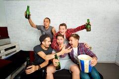 Los muchacho-fans jovenes ven la TV, se relajan, se divierten y beben la cerveza amigo Imagen de archivo