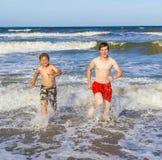 Los muchachos adolescentes se divierten durante día de fiesta de la playa Foto de archivo libre de regalías