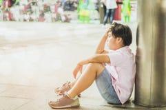 Los muchachos asiáticos sientan la tensión y el mal humor solamente en el espacio abierto de la escuela, el concepto de ser cinis foto de archivo libre de regalías