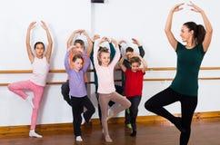 Los muchachos concentrados y las muchachas que ensayan ballet bailan en estudio Foto de archivo libre de regalías