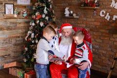 Los muchachos de los pequeños hermanos enseñan a Santa Claus a jugar en la tableta en fest Imagen de archivo