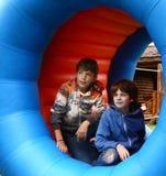 Los muchachos del preadolescente en parque de atracciones en caucho del balanceo barrel Fotografía de archivo libre de regalías