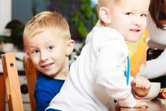 Los muchachos embroman a los niños que comen la comida del desayuno de las avenas en la tabla Fotografía de archivo