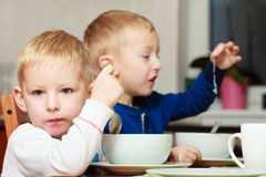 Los muchachos embroman a los niños que comen la comida del desayuno de las avenas en la tabla Foto de archivo