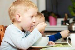Los muchachos embroman a los niños que comen la comida del desayuno de las avenas en la tabla Imagen de archivo libre de regalías
