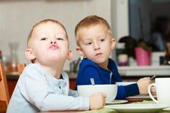 Los muchachos embroman a los niños que comen la comida del desayuno de las avenas en la tabla Fotos de archivo libres de regalías