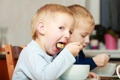 Los muchachos embroman a los niños que comen la comida del desayuno de las avenas en la tabla Imagenes de archivo