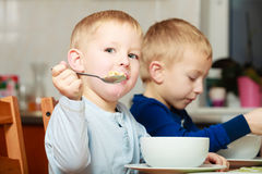 Los muchachos embroman a los niños que comen la comida del desayuno de las avenas en la tabla Fotos de archivo