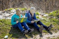 Los muchachos en caretas antigás en descarga de basura leyeron los libros Encuesta ambiental foto de archivo