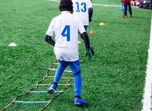 Los muchachos en la forma blanca y azul del deporte del fútbol hacen ejercicios en campo verde Fútbol para los niños, forma de vi fotos de archivo