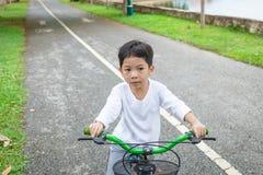 Los muchachos están completando un ciclo en el detalle del parque de la salud Imagen de archivo libre de regalías