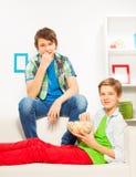 Los muchachos felices comen las palomitas mientras que se sientan en el sofá blanco Imágenes de archivo libres de regalías