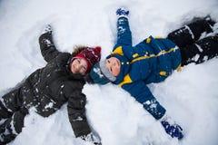 Los muchachos felices en nieve juegan y sonríen día soleado fotografía de archivo libre de regalías
