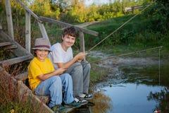 Los muchachos felices van a pescar en el río, dos niños del fisherma Foto de archivo libre de regalías