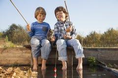 Los muchachos felices van a pescar en el río, dos niños del pescador w Imagen de archivo