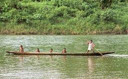 Los muchachos indios navegan con la canoa de cobertizo en el río, Nicaragua Fotografía de archivo
