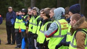 Los muchachos jovenes en uniiform del rescate permanecen en línea en la calle grupo Práctica de Emercom metrajes