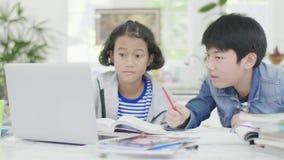 Los muchachos jovenes están utilizando los ordenadores para enseñar y para explicar a la preparación A los amigos con expresiones almacen de video