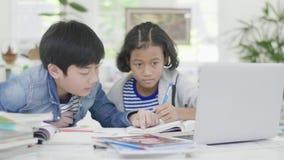 Los muchachos jovenes est?n utilizando los ordenadores para ense?ar y para explicar a la preparaci?n A los amigos con expresiones almacen de metraje de vídeo