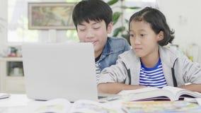 Los muchachos jovenes est?n utilizando los ordenadores para ense?ar y para explicar a la preparaci?n A los amigos con expresiones metrajes