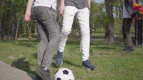 Los muchachos jovenes juegan a fútbol en el parque Reconstrucci?n al aire libre almacen de metraje de vídeo