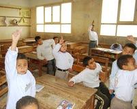 Los muchachos jovenes que aumentan las manos para contestan a la pregunta imagen de archivo libre de regalías