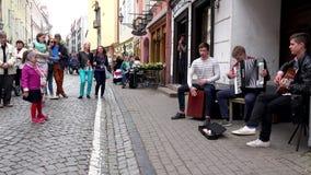 Los muchachos jovenes tocan los instrumentos musicales contra la audiencia de la gente Panorama metrajes