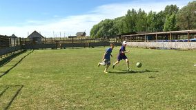 Los muchachos juegan a fútbol en un campo de fútbol en el parque en un día de verano almacen de video