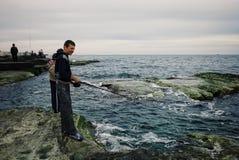 Los muchachos locales están pescando para la cena en la orilla del mar Caspio en donde las reuniones del desierto y del agua imagen de archivo