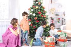 Los muchachos miran muchos regalos un árbol de abeto de Cristmas Imágenes de archivo libres de regalías