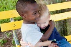 Los muchachos multirraciales se abrazan Fotografía de archivo
