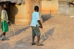 Los muchachos no identificados de Dagomban juegan con los palillos de madera en el local fotografía de archivo libre de regalías