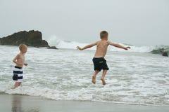 Los muchachos que saltan en el agua en la playa Imagenes de archivo