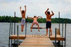 Los muchachos que saltan en el lago Imagen de archivo libre de regalías