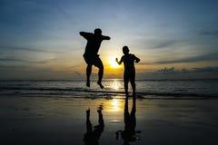 Los muchachos que saltan en la puesta del sol de la playa Fotografía de archivo libre de regalías