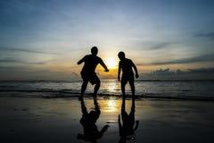Los muchachos que saltan en la puesta del sol de la playa Imágenes de archivo libres de regalías