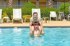 Los muchachos se divierten que juega a cuestas en la piscina Imágenes de archivo libres de regalías