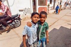 Los muchachos se encuentran en la calle estrecha de la ciudad india con tráfico del transporte en el día caliente en el estado de Foto de archivo
