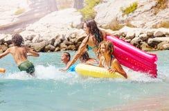Los muchachos y el funcionamiento de las muchachas saltan en el mar en una playa Foto de archivo libre de regalías
