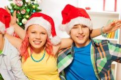 Los muchachos y la muchacha adolescentes en Año Nuevo van de fiesta Imagen de archivo libre de regalías