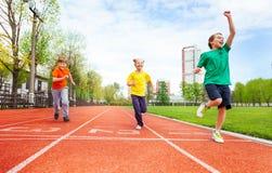 Los muchachos y la muchacha en uniformes coloridos funcionan con maratón Fotos de archivo libres de regalías